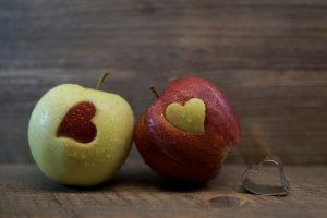 2 apples, one green and one red. Both have heart-shaped cut-outs that have been replaced b the cut-out of the other apple.