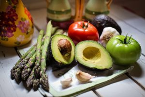 Image of avocado, asparagus, apple, garlic, on a cutting board