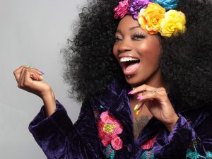 Beautiful Lady with Colorful flowers on her head, black robe with large flower print, big curly afro, and a large, beautiful smile