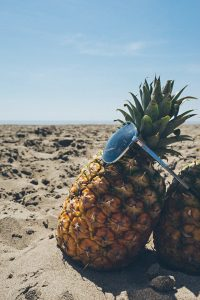 Picture of a pineapple leaning against another pineapple or a beach with shades on.
