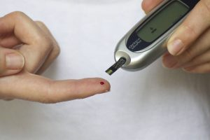 Woman testing blood sugar level with drop of blood from finger