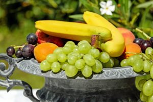 Fruit bowl that has grapes, bananas, nectarines, and apples