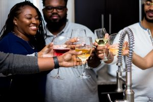 Group of people smiling while toasting with wine glasses