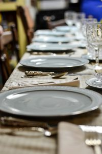 plates and silverware lined up at a holiday table