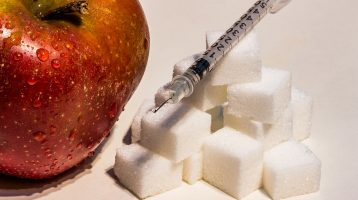 Image of insulin syringe sitting on top of sugar cubes next to a red apple
